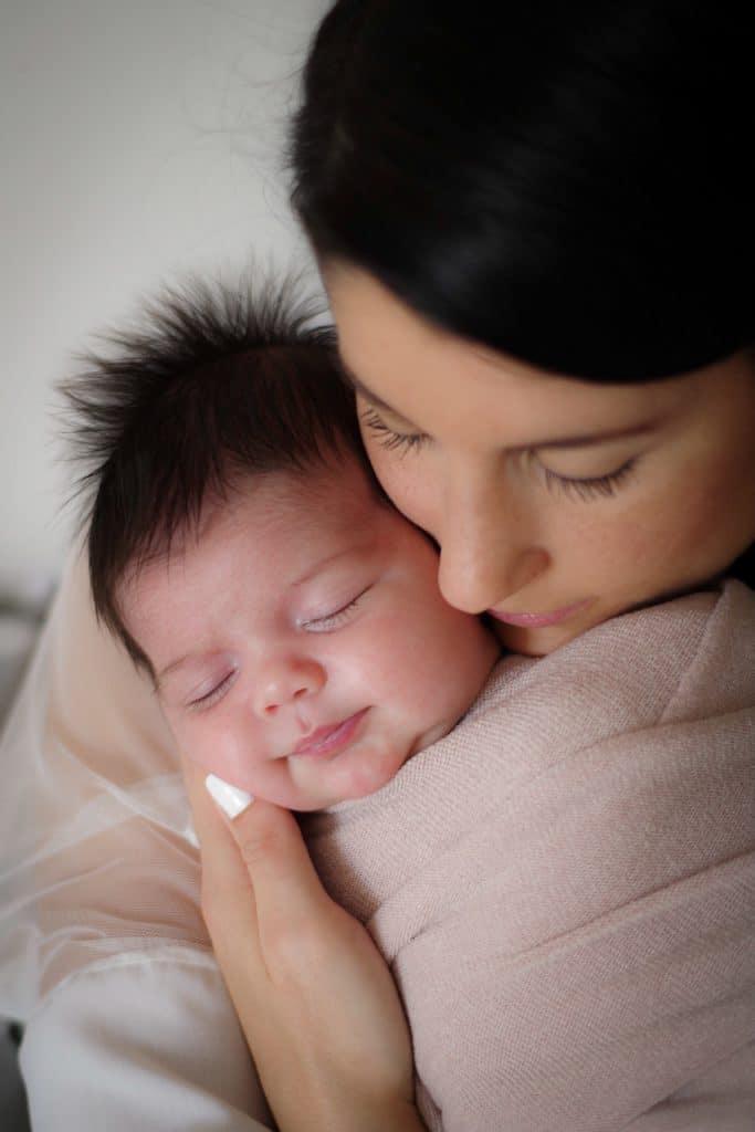 bébé emmailloté beige cheveux noir bras maman