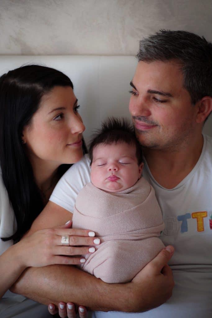 nouveau né emmailloté bras parents regard