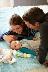 bébé caresse parents penchés chenille doudou